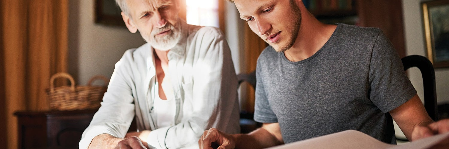 Father and son looking over paperwork together