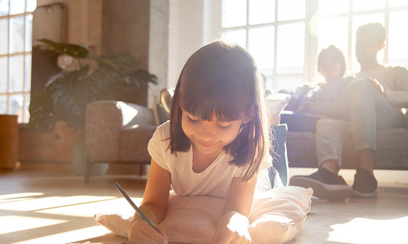 Girl reading a book and spending time with parents.