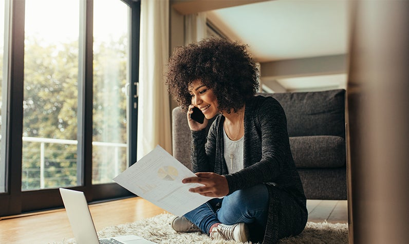 A woman surveying financial information while sitting on the floor of her new home.