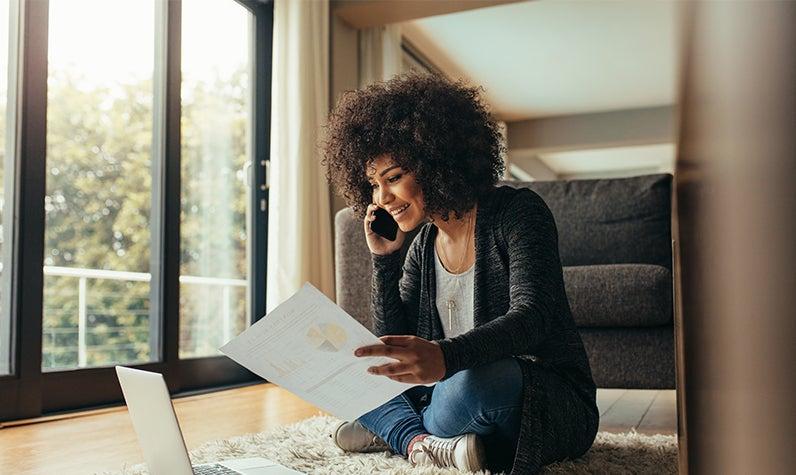 Una mujer examinando información financiera mientras estaba sentada en el piso de su nuevo hogar.