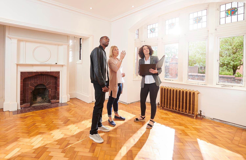 A couple surveys a house with a realtor.