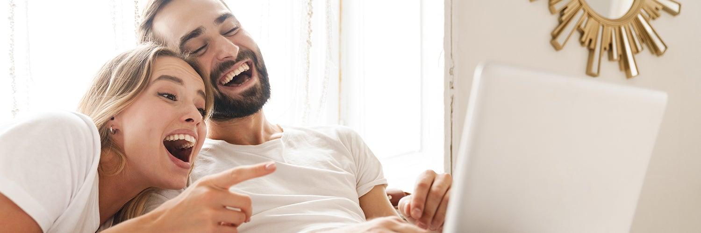Una pareja mira la pantalla de una computadora y se ríe.