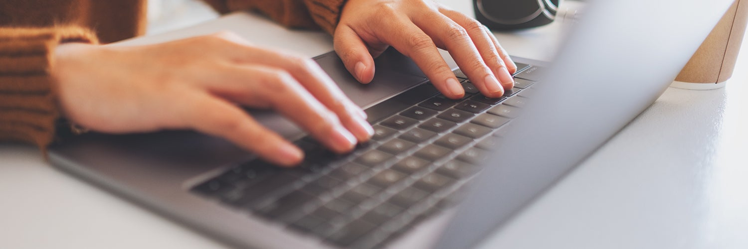 A person's hands typing on a laptop keyboard.