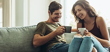 man and woman on couch enjoy a beverage